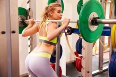 Vrouwengewichtheffen barbells bij een hurkend rek in een gymnastiek stock foto's