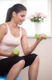 Vrouwengewichtheffen. Mooie jonge vrouwen die thuis uitoefenen  Stock Afbeeldingen