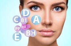 Vrouwengezicht met vitaminenpictogrammen Gezond huidconcept stock foto's