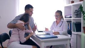 Vrouwengezondheid, gefrustreerd paar met de zitting van het onvruchtbaarheidsprobleem voor hun vrouwelijke arts op medisch kantoo stock videobeelden