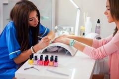 Vrouwenhand bij de manicurebehandeling in schoonheidssalon E Stock Foto's
