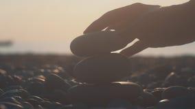Vrouwenhand de bouwtoren van kiezelstenen op strand bij zonsondergang Ontspanning bij strand stock footage