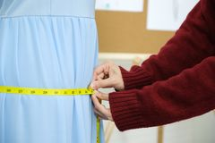 Vrouwenhand die blauwe kleding, kleine bedrijfseigenaar, het concept van de manierindustrie meten stock foto