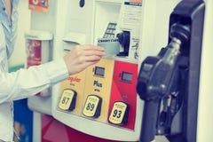 Vrouwenhand die creditcard jatten bij benzinepomppost royalty-vrije stock afbeeldingen