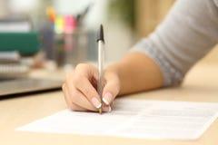Vrouwenhand die of in een document schrijven ondertekenen Stock Afbeelding