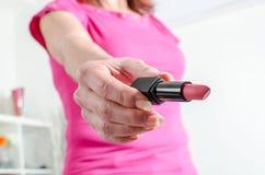 Vrouwenhand die een lippenstift houden stock foto