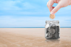 Vrouwenhand die een muntstuk op de achtergrond van de strandaard, besparing, het concept van het Besparingsgeld zetten stock afbeelding