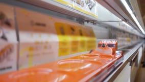 Vrouwenhand die een plaat van Sushibroodjes nemen stock footage
