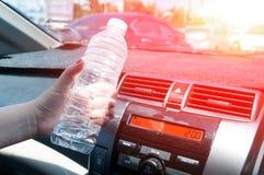 Vrouwenhand die een plastic fles water in auto houden royalty-vrije stock foto