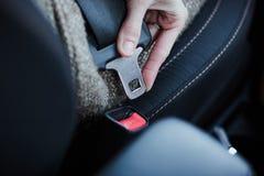 Vrouwenhand die een veiligheidsgordel in de auto vastmaken royalty-vrije stock afbeeldingen