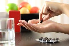 Vrouwenhand die een vitamine complexe pil vangen royalty-vrije stock afbeeldingen