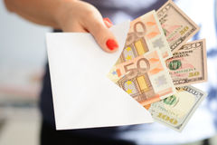 Vrouwenhand die en een wit envelophoogtepunt die van geld houden overgaan witwassen van geld, onwettige contant geldoverdracht vo Royalty-vrije Stock Afbeelding