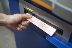 Vrouwenhand die geld van bankatm machine terugtrekken stock foto's