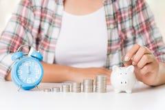 Vrouwenhand die geldmuntstuk zetten in spaarvarken en stapel muntstukken royalty-vrije stock afbeelding