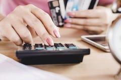 Vrouwenhand die haar uitgaven en schuld van creditcards berekent royalty-vrije stock fotografie