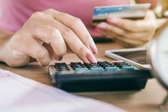 Vrouwenhand die haar uitgaven en schuld van creditcards berekent stock foto