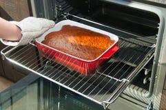 Vrouwenhand die hete pastei van de oven nemen Royalty-vrije Stock Afbeelding