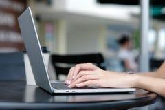 Vrouwenhand die laptop computer met behulp van bij in openlucht achtergrond, mensen en technologie, levensstijlen stock foto's