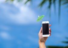 Vrouwenhand die mobiele telefoon en cocktailparaplu tonen stock afbeeldingen