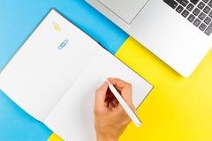 Vrouwenhand die in notitieboekje over blauwe en gele achtergrond schrijven Hoogste mening Stock Foto