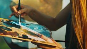 Vrouwenhand die olieverven op houten palet mengen Creatief kunstenaar het schilderen beeld stock videobeelden