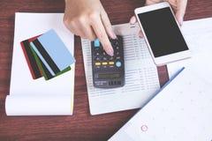 Vrouwenhand die slimme telefoon houden die haar maandelijkse uitgaven met creditcard berekenen, die rekeningsboek, het concept FO royalty-vrije stock foto
