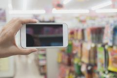 Vrouwenhand die slimme telefoon in supermarkt het winkelen houden Royalty-vrije Stock Foto's