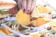 Vrouwenhand die snel voedselhamburger, chips, frieten en zoete drank op houten lijst eten Stock Fotografie