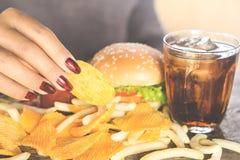 Vrouwenhand die snel voedselhamburger, chips, frieten en zoete drank op houten lijst eten Royalty-vrije Stock Fotografie