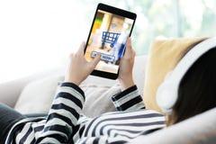 Vrouwenhand die tablet met het winkelen online apparaat op het schermbedelaars gebruiken stock fotografie