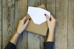 Vrouwenhand het openen envelop op houten lijst stock foto