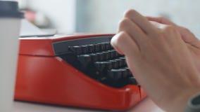 Vrouwenhand het typen op rode uitstekende schrijfmachine stock videobeelden
