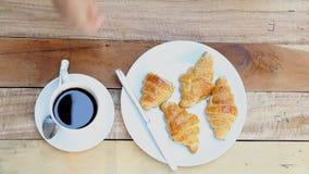 Vrouwenhand met een kop van zwarte koffie en een vers gebakken croissant stock footage