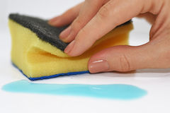 Vrouwenhand met het schoonmaken van spons en blauwe vloeistof stock foto