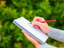 Vrouwenhand met rood potlood die op notitieboekje in landbouwtuin schrijven stock afbeeldingen