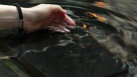 Vrouwenhand met waterplons, backlit door de avondzon Mooie gelooide handen van een jonge vrouw stock videobeelden
