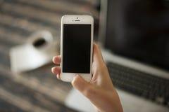Vrouwenhand mobiele telefoon houden, en laptop en koffiekop die in bedelaars Stock Foto's