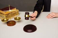 Vrouwenhand ongeveer om hamer op klinkend blok in de rechtszaal te bonzen royalty-vrije stock fotografie