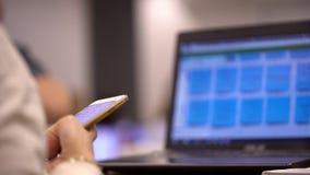 Vrouwenhanden die aan laptop werken en slimme telefoon houden De onderneemster overhandigt multitasking gebruikend draagbare comp stock video