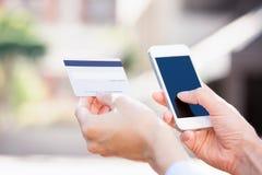 Vrouwenhanden die creditcard houden en cel, slimme telefoon gebruiken royalty-vrije stock foto's
