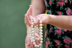 Vrouwenhanden die de juwelen van parelparels houden Close-up van vrouwelijke hand met pareljuwelen Vrouwelijke hand die een koord Stock Foto's