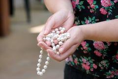 Vrouwenhanden die de juwelen van parelparels houden Close-up van vrouwelijke hand met pareljuwelen Vrouwelijke hand die een koord Royalty-vrije Stock Fotografie