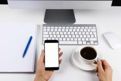 Vrouwenhanden die de telefoon met het geïsoleerde scherm en kop van koffie houden Bedrijfswerkplaats met toetsenbord en bedrijfsv royalty-vrije stock afbeelding