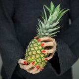 Vrouwenhanden die een ananas, sensueel studioschot houden Royalty-vrije Stock Afbeelding