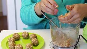 Vrouwenhanden die een bal van pinda's en andere ingrediënten vormen De spatie voor cake knalt Daarna op de plaat zijn kant-en-kla stock footage