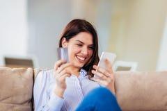 Vrouwenhanden die een creditcard houden en smartphone voor online het winkelen met behulp van royalty-vrije stock afbeeldingen