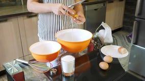 Vrouwenhanden die een ei in een kom barsten Het scheiden van dooier van proteïne stock footage