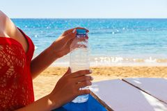Vrouwenhanden die een fles water in openlucht op het strand openen royalty-vrije stock afbeelding
