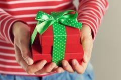 Vrouwenhanden die een gift of een huidige doos met boog van groen lint houden stock foto's