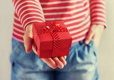 Vrouwenhanden die een gift of een huidige doos met boog van rood lint houden Royalty-vrije Stock Afbeeldingen